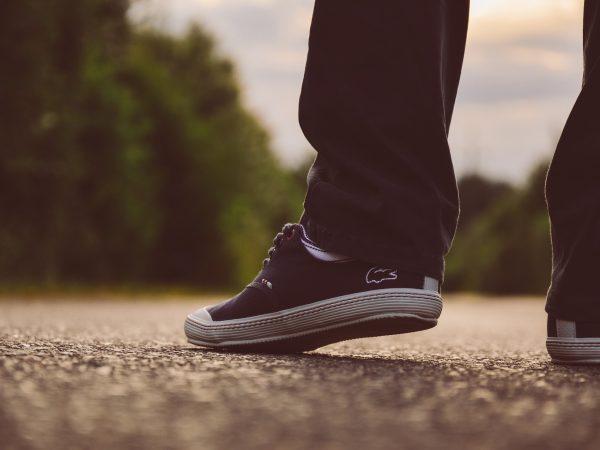 Homem andando em uma estrada calçando par de tênis Lacoste azul