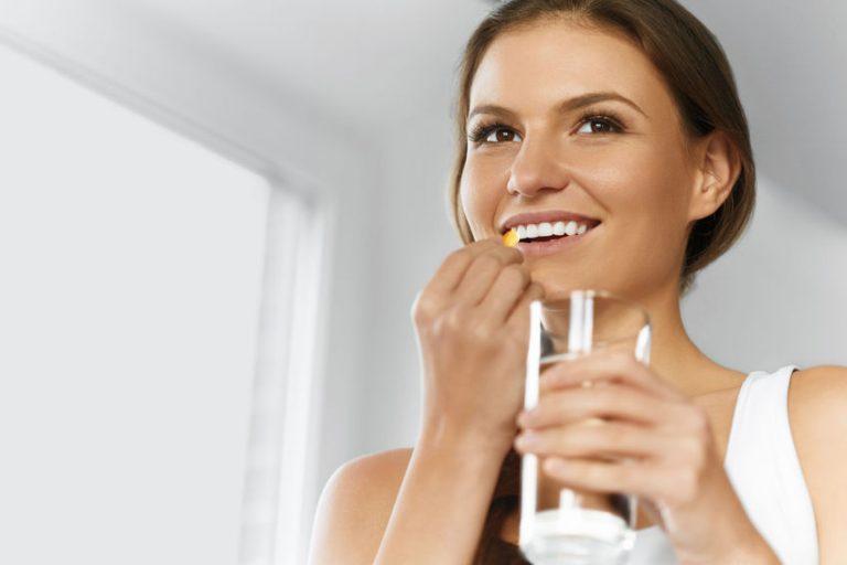 Foto de uma mulher sorridente, que não está olhando para a câmera, levando até a boca com uma das mãos uma cápsula semelhante a uma cápsula de óleo de linhaça. Na outra mão, ela segura um copo d'água.