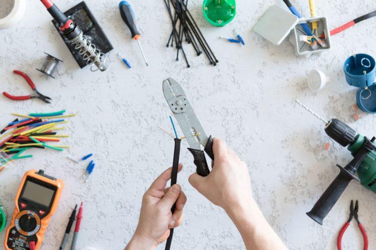 Uma pessoa segurando um fio e um alicate desencapador, rodeada por outras ferramentas.