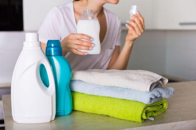 Imagem de mulher cheirando o perfume de um amaciante com embalagens e toalhas coloridas sobre a mesa