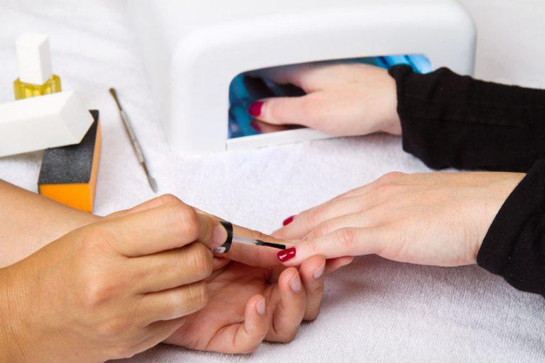 Foto de uma manicure pintando as unhas da mão de uma mulher de vermelho, enquanto a mulher coloca a outra mão dentro de uma cabine de led.