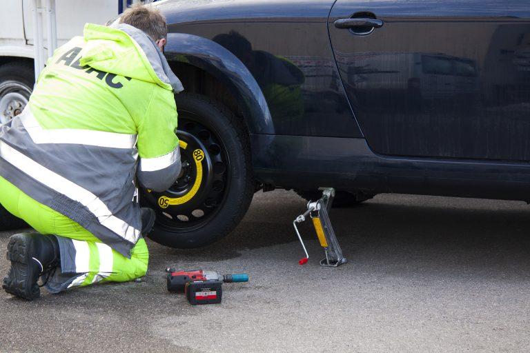 Um homem trocando um pneu. O carro está levantado por um macaco. No chão existe uma parafusadeira elétrica