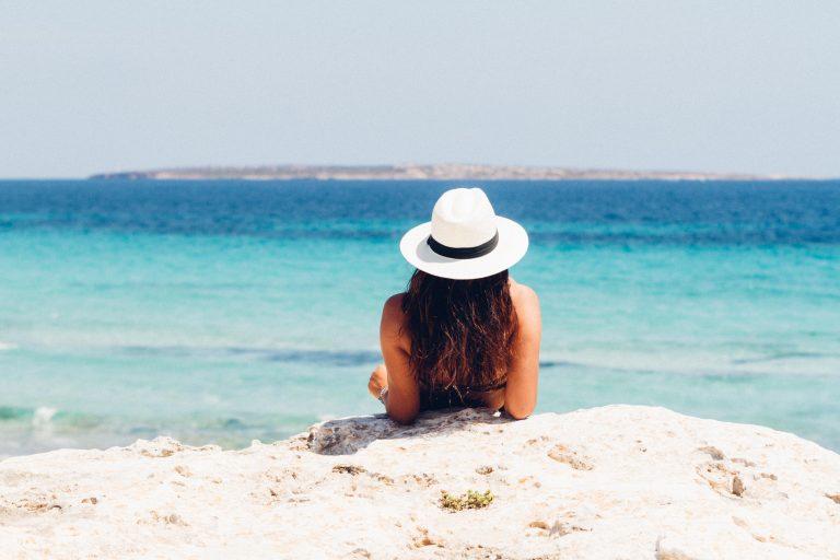 Foto de uma mulher de cabelos castanhos semi deitada na areia da praia, com os dois cotovelos apoiados no chão. Ela está olhando em direção ao mar azul e usa um chapéu branco com faixa preta.