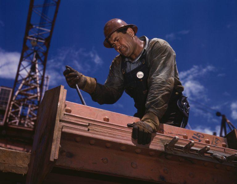 Um homem usando a chave catraca para parafusar um parafuso grande em um bloco de metal.