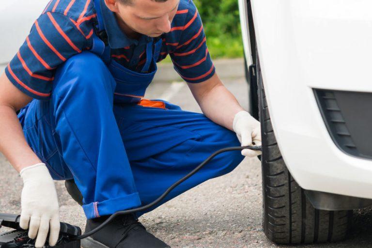 Um homem usando compressor portátil para calibrar um pneu em um carro.