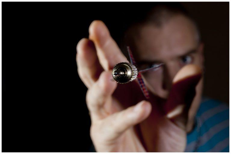 Imagem aproximada de dardo sendo lançado por jogador
