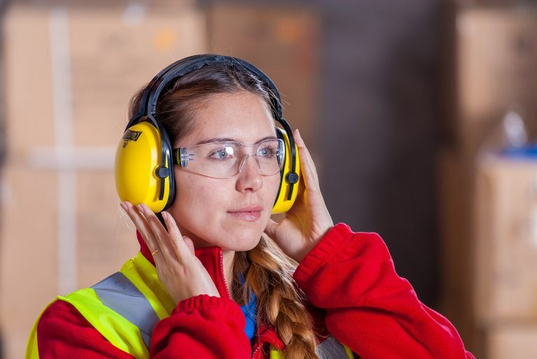 Uma mulher com roupa de operária, óculos de proteção transparente e protetor de ouvidos na cor amarela.