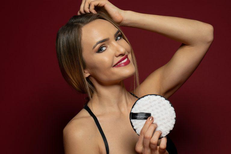 Foto com blur, que mostra uma mulher com blusa de gola alta vermelha se olhando em um pequeno espelho de maquiagem, enquanto segura algum objeto.