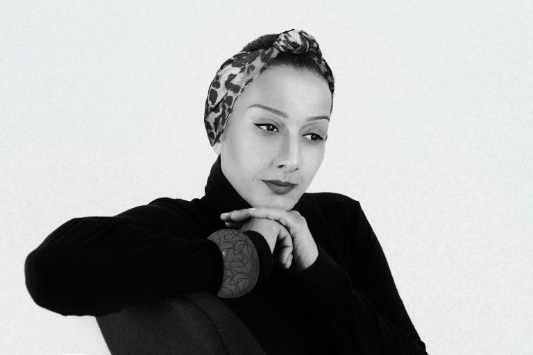 Foto em preto e branco de uma mulher sentada em uma cadeira, com o braço apoiado no encosto, o olhar longe, vestindo blusa de gola alta, pulseira grande, e uma faixa de cabelo estampada.