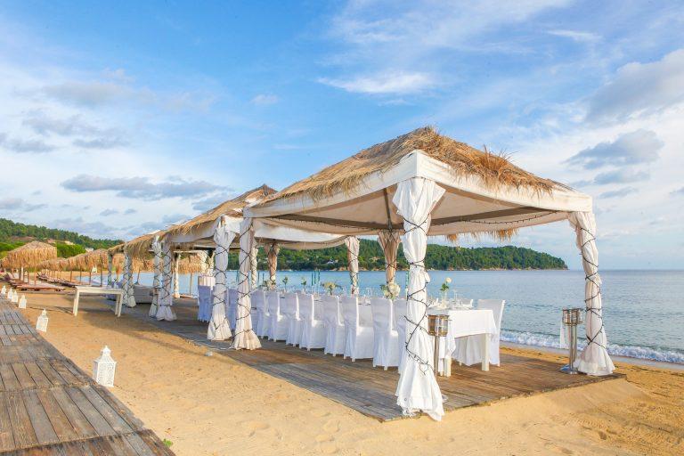 Imagem de gazebos dobráveis decorados com tecidos e luzes, sendo utilizados em evento na praia.