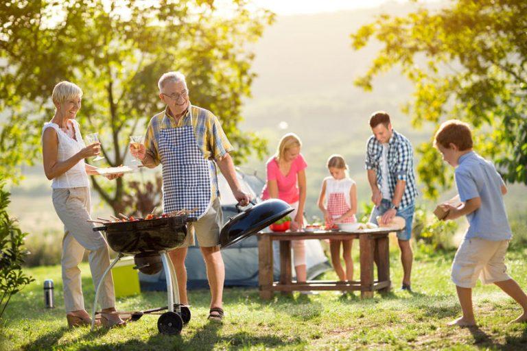Na esquerda há uma churrasqueira, uma mulher e um homem, ambos idosos. Ao lado direito existe um casal adulto que corta alimentos em uma mesa junto com uma pré-adolescente, e, um garoto descalço segurando uma tábua de madeira.