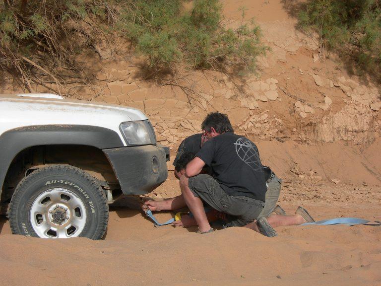 Um homem prendendo um guincho na frente de um carro que está preso na terra.