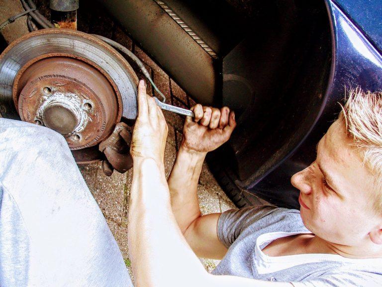 Um homem usando uma chave de aperto para trocar o freio a disco de um carro