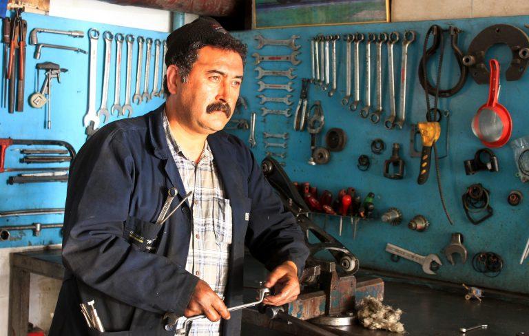 Um mecânico com diversas chaves nos bolsos da camisa de manga longa em uma oficina que também tem nas paredes diferentes chaves penduradas em pregos.