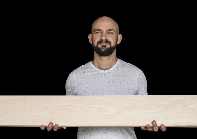 Um homem careca e barbudo segurando uma tábua de madeira.