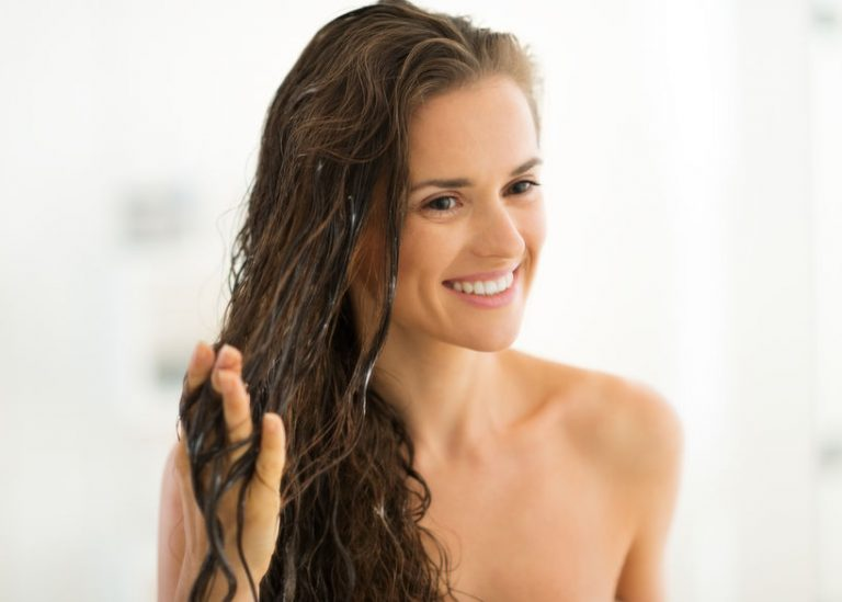 Foto de uma mulher aparentemente nua, aplicando máscara capilar em seus cabelos ondulados e sorrindo.