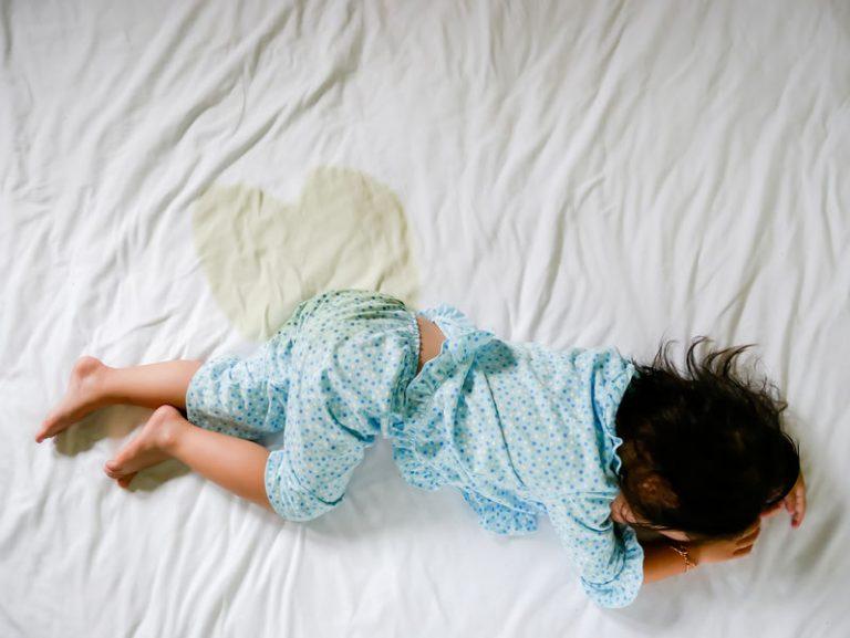 criança dormindo com marca de xixi em forma de coração no lençol