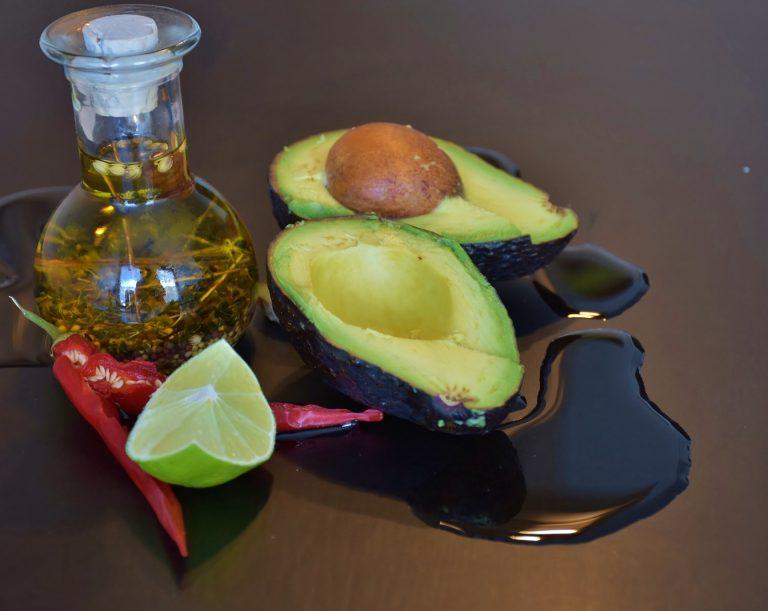 Imagem de óleo de abacate com ervas em frasco de vidro com abacates, limão e pimentas cortadas