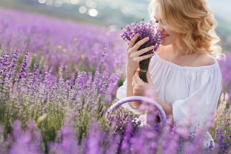 Imagem de uma mulher loira em meio a uma plantação de lavanda, com um bouquet da planta nas mãos. Ela está sorridente e cheirando o bouquet.