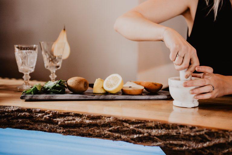 Imagem de pessoa usando um pilão branco sobre mesa de madeira