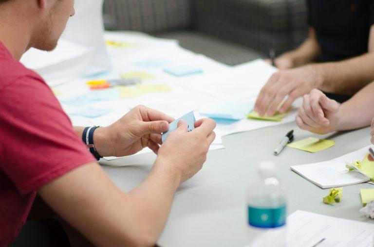 Foto que mostra os braços de três pessoas ao redor de uma mesa, com papéis espalhados, escrevendo e organizando post-its coloridos.