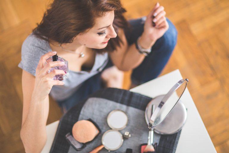 Foto de uma mulher sentada em frente a uma bancada com maquiagens e um espelho, enquanto aplica perfume em seu pescoço.