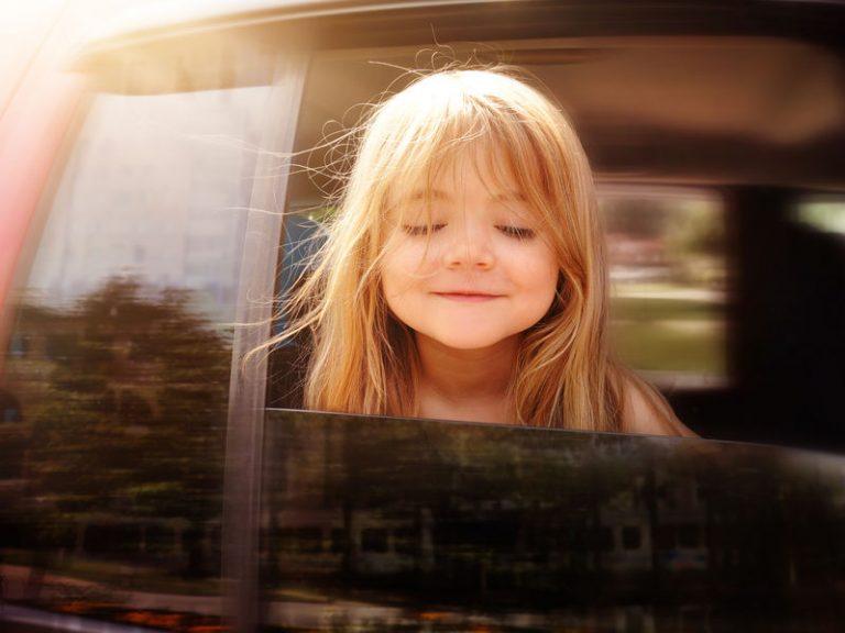Uma menina pequena com o rosto próximo de uma janela aberta no banco traseiro de um carro em movimento