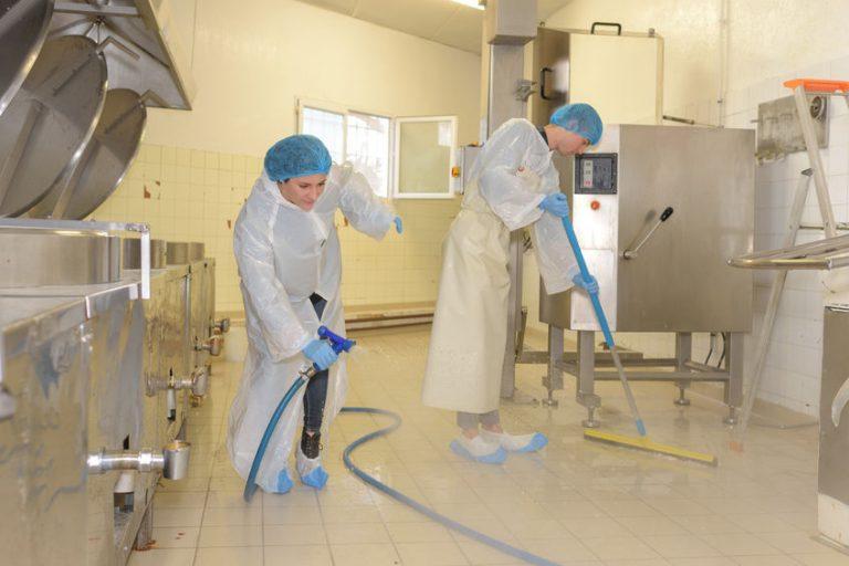 Um homem e uma mulher com roupas brancas limpando uma cozinha. Ele usa um rodo grande. Ela utiliza uma mangueira