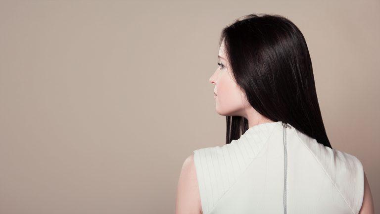 Foto de uma mulhe de costas, com a cabeça virada para o lado, e o cabelo preto liso jogado para frente.