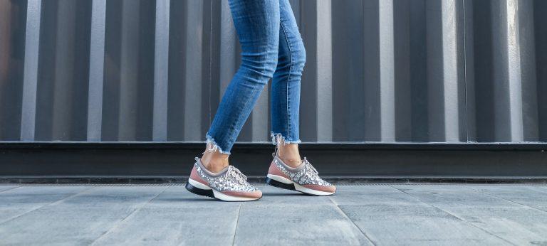 Foto de mostra do meio das coxas pra baixo, de uma pessoa que está de lado, usando calça jeans e tênis colorido com aplicações.