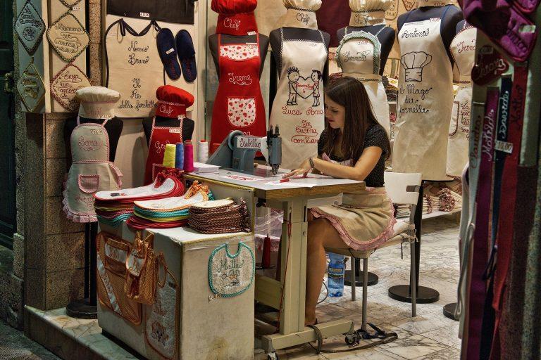 Imagem mostra uma mulher trabalhando em um ateliê de costura.