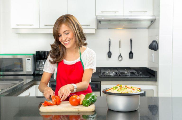 Foto que mostra una mulher, do peito para baixo, de avental, jogando repolho roxo em uma panela que está em uma boca de fogão ligada. Ele usa anéis nas mãos.