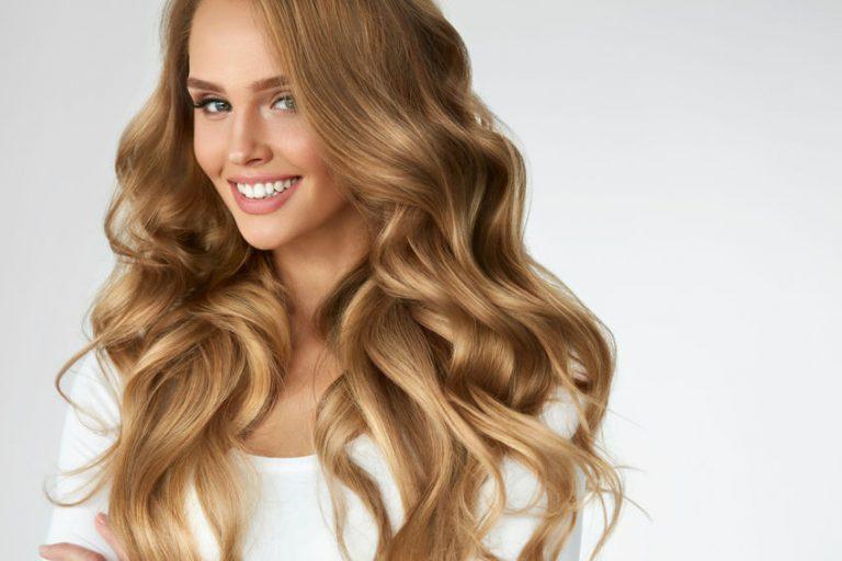Mulher com cabelos longos ondulados sorrindo.