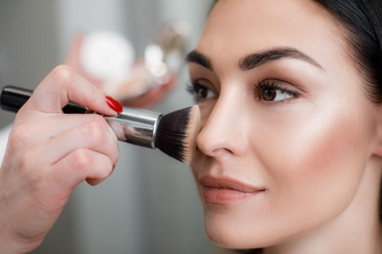 Imagem de uma mulher sendo maquiada.