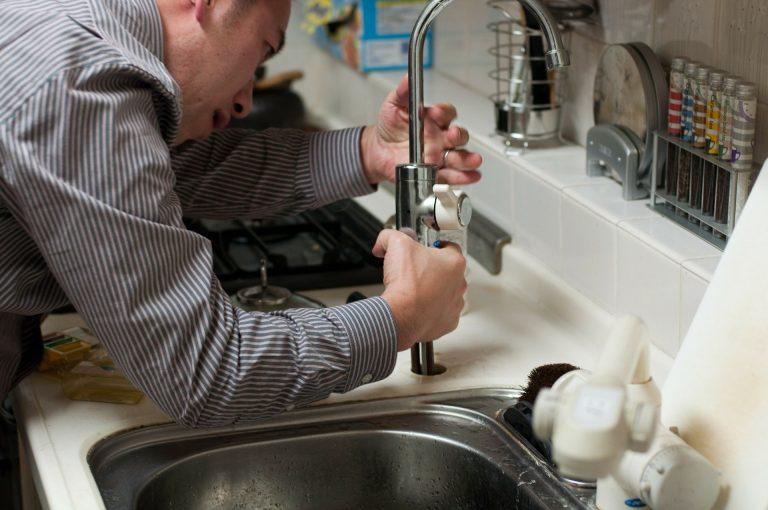Imagem mostra um homem mexendo na torneira de uma pia de cozinha.