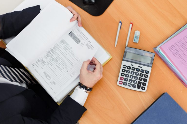 Imagem mostra uma pessoa em uma mesa de trabalho com uma calculadora ao lado.