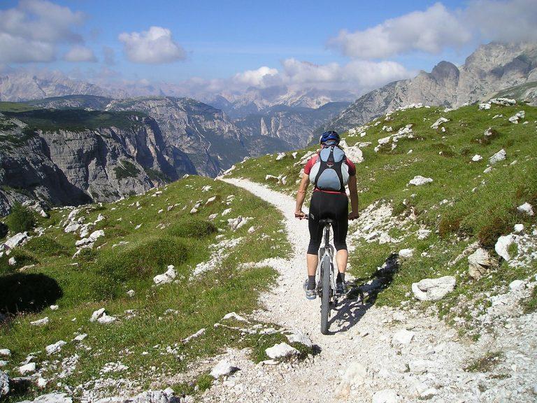 Imagem mostra uma pessoa subindo uma montanha com uma bicicleta.
