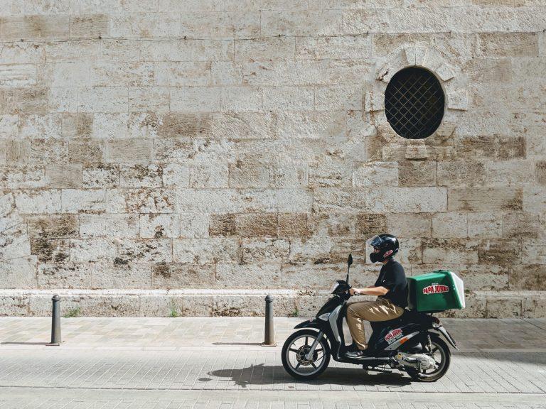 Imagem mostra um homem pilotando uma moto com uma cesta de entrega.