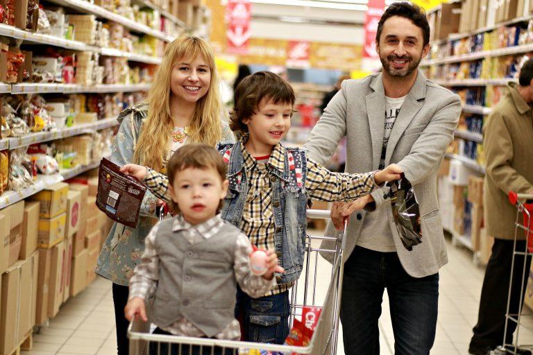Imagem de família fazendo em supermercado com duas crianças no carrinho de compra