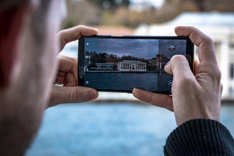 Homem tirando foto com celular de tela infinita.