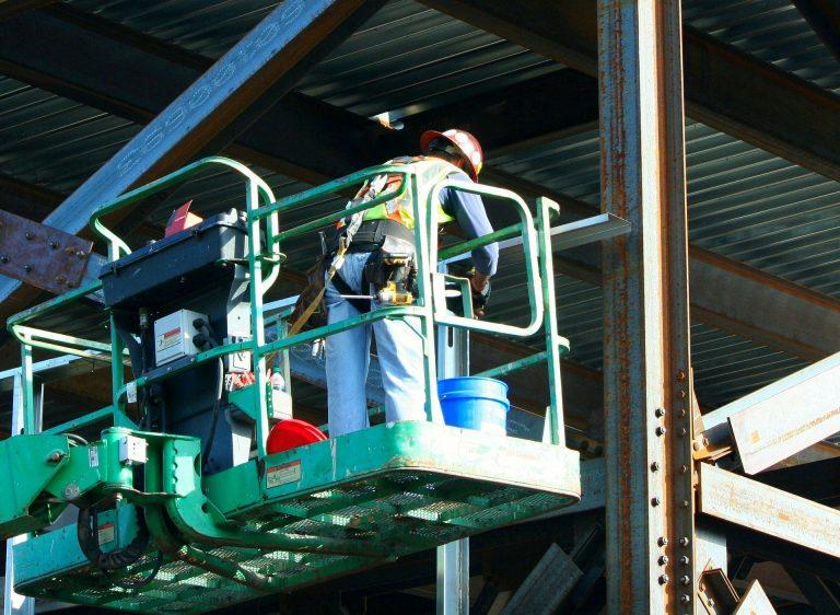 Imagem mostra um trabalhador usando um cinto de ferramentas em uma plataforma elevada.
