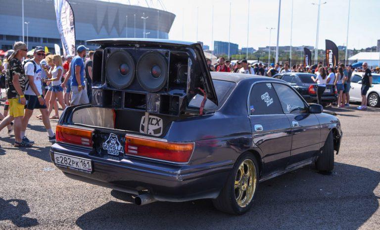 Imagem mostra várias pessoas ao redor de um carro com grande aparato sonoro.