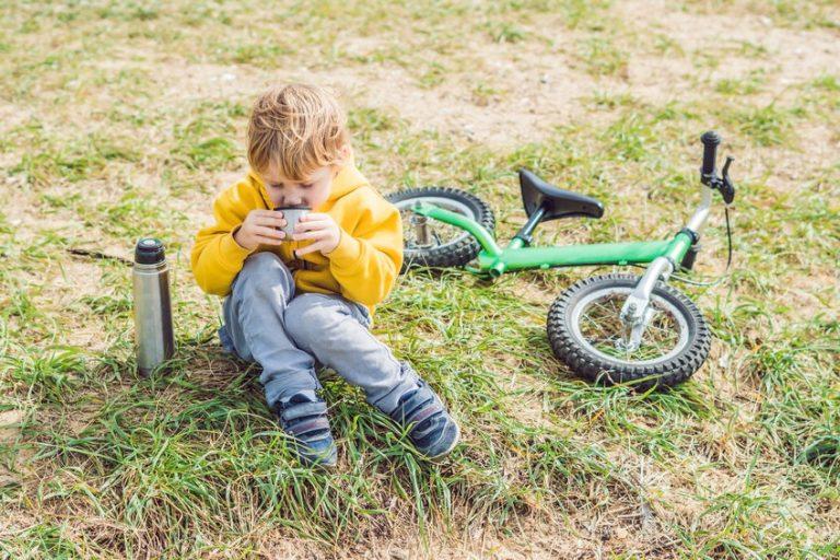 Criança sentada na grama, tomando água na garrafa térmica, com bicicleta ao lado.