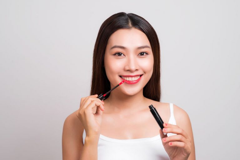 Mulher aplicando lip tint nos lábios.