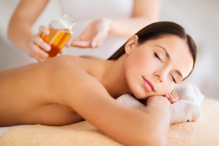 Foto de uma mulher deitada em um local confortável, relaxando e aguardando para receber uma massagem com algum óleo.