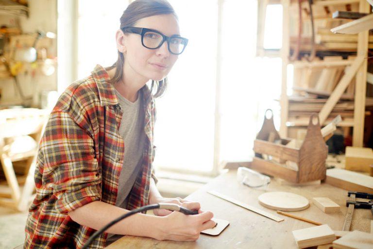 Imagem mostra uma mulher fazendo desenho em madeira com um pirógrafo.