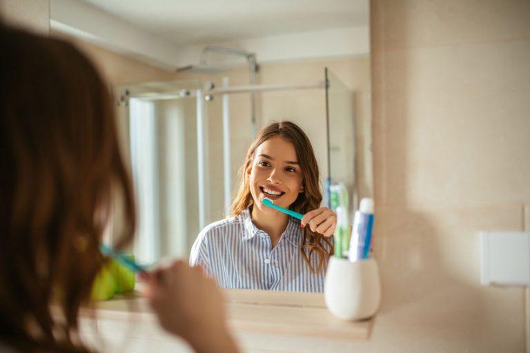Moça escova dentre em frente ao espelho com porta-escovas ao lado