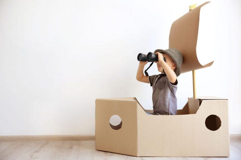 criança brincando de navegador em um barco de papelão.
