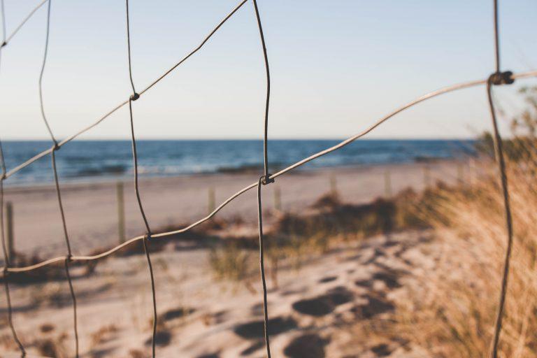 Imagem aproximada de cerca rússtica de arame galvanizado próxima ao mar
