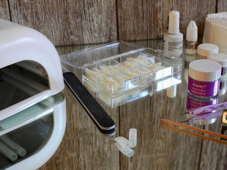Foto de uma mesa espelhada com uma cabine de led, uma lixa, várias unhas postiças e outros cosméticos e ferramentas necessárias para a realização da unha em gel.